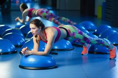Powerful attractive muscular woman fitness trainer w orking out Stock Photos