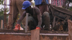 A construction worker uses a long board to screed concrete. Stock Footage