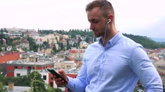 Young handsome business man listens music with earphone on smartphone - city Stock Footage