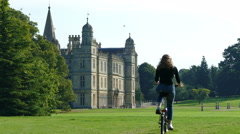 Young woman riding bicycle past Burghley House, England (1). Stock Footage