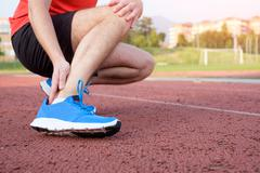 Runner with injured ankle on the track Stock Photos