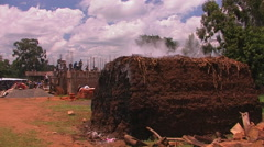 Men are constructing a building, and steam is coming off a large pile of dirt. Stock Footage