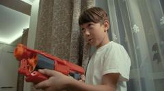 Young boy playin with a toy gun at home Stock Footage