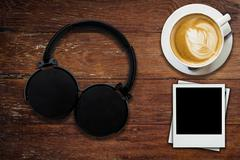 Headphone coffee and photo frame on wood background and texture Stock Photos