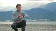 Young handsome man sitting on the rocky beach. He checks messages on the smart Stock Footage
