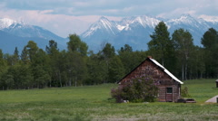 Small wood cabin with mountain backdrop Stock Footage