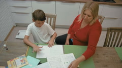 Mother and son are doing homework for school at the kitchen Stock Footage