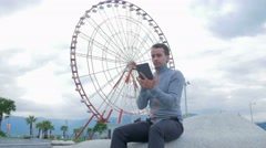 A young man checks the messages on the Tablet PC around the Ferris wheel. Early Stock Footage