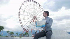 Young handsome man looking for landmarks on a paper map nearby ferris wheel Stock Footage