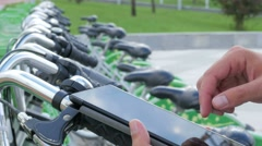 A man checks the messages on the Tablet PC on a bike parking lot. He's going to Stock Footage