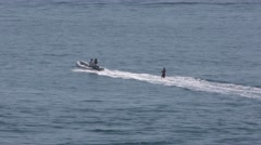 Tracking shot of water skier in open  ocean being pulled by a motorized dingh Stock Footage
