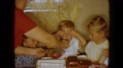 1959: parent calms a young unhappy child with a lollipop while several children Stock Footage