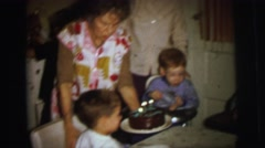 1972: a family gathered around a table as the birthday boy prepares to blow out Stock Footage