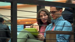 Young girl and nerdy man in glasses using tablet computer together in a cafe. 4K Stock Footage