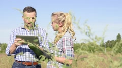 Farming instructor with apprentice in agricultural field Stock Footage