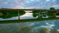 Flying under bridge over tranquil waters reflecting sky at dawn Stock Footage