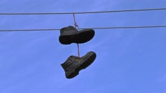Old boots hanging on an electric wire Stock Footage