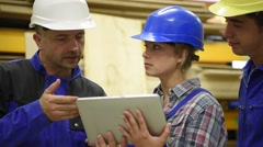 Carpentry teacher using tablet to train apprentice Stock Footage