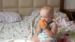 A handsome baby eating a peach on a breakfast in bed. He tears off a piece and Stock Footage