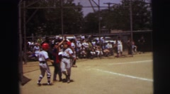 1972: an older boy in a gray baseball uniform and red batters cap is up to bat Stock Footage