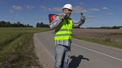 Road construction worker with traffic cone on shoulder show o.k. gesture Stock Footage