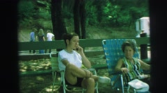 1972: stranger films young girl at picnic park sitting with an elderly woman  Stock Footage