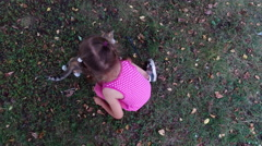 Girl child in glasses plays with a gray kitten in the yard. Stock Footage