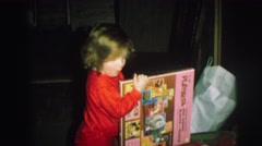 1972: several children open gifts accompanied by an adult woman  Stock Footage
