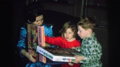 1972: childrens are playing with his mother using books LYNBROOK, NEW YORK Stock Footage