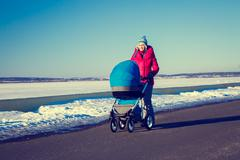 Mother with Baby Stroller Walking in Winter Park Stock Photos