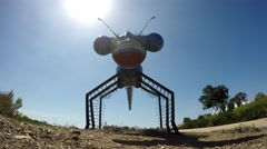 Dragonfly made out of car parts stands guard on a hill with the sun behind.mp Stock Footage