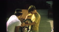 1972: a boy and his father repair a bicycle LYNBROOK, NEW YORK Stock Footage