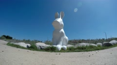 White rabbit statue stands guard on a bike path Stock Footage