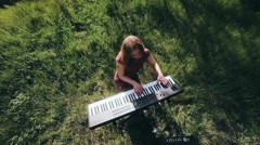 Girl in the forest plays the synthesizer and sings Stock Footage