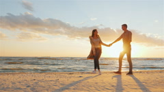 Steadicam shot: Loving couple walking at sunset on the beach or lake. She leads Stock Footage