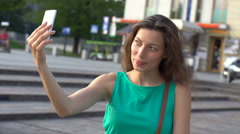 Pretty girl doing selfies on smartphone in town, steadycam shot, slow motion sho Stock Footage