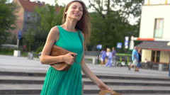 Happy girl waving his curly hair in the city, steadycam shot, slow motion shot a Stock Footage