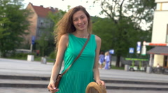 Happy girl going round and smiling to the camera, steadycam shot, slow motion sh Stock Footage