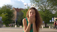 Happy girl sending kisses to camera, steadycam shot, slow motion shot at 240fps Stock Footage