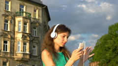Pretty girl moving while listening music and browsing internet on smartphone Stock Footage