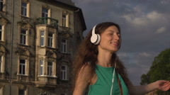 Happy girl going round while listening music, steadycam shot, slow motion shot a Stock Footage