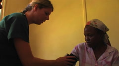 A medical worker checks the blood pressure of an African woman. Stock Footage