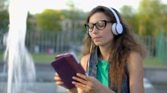 Pretty girl listening music and using tablet next to the fountain Stock Footage