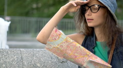 Absorbed tourist reading map next to fountain, steadycam shot, slow motion shot  Stock Footage