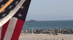 Newport Beach Pier in background with American flag blowing in the wind and r Stock Footage