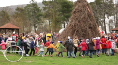 Children dance in a circle around the effigy of Maslenitsa Stock Footage