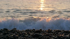 Seascape with orange sky at sunset. Waves beat against the rocky beach Stock Footage