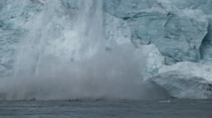 Close of falling ice splashing into water below. Stock Footage