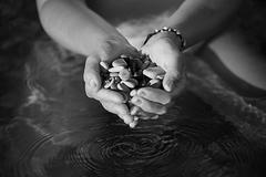 Black and white image of clasped hands with the sea stones on the background Stock Photos