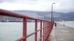Tourist goes on the breakwater Stock Footage
